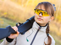 Girl with a shotgun. Young beautiful girl with a shotgun in an outdoor Royalty Free Stock Photography