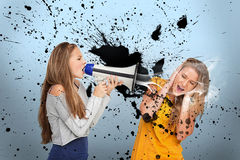 Girl shouting at another through megaphone Stock Photo