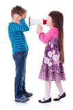 Girl shouting at boy with megaphone. Little girl shouting at boy with megaphone Stock Photo