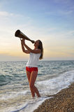 Girl shouting into a megaphone. At sea Royalty Free Stock Photography