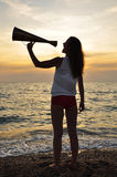 Girl shouting into a megaphone. At sea Stock Photo