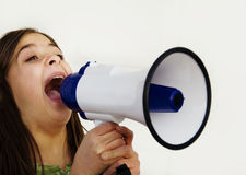 Girl shouting through megaphone. Over white background Stock Photo
