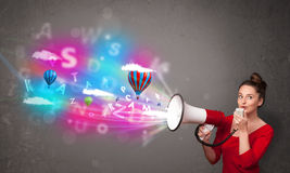 Girl shouting into megaphone and abstract text and balloons come Stock Photography