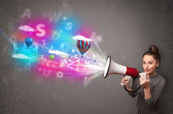 Girl shouting into megaphone and abstract text and balloons come Royalty Free Stock Images