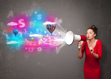 Girl shouting into megaphone and abstract text and balloons come Stock Photo