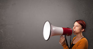 Girl shouting into megaphone on copy space background Royalty Free Stock Photography