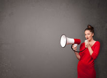 Girl shouting into megaphone on copy space background Royalty Free Stock Image