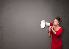 Girl shouting into megaphone on copy space background Stock Photo