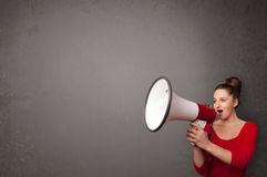 Girl shouting into megaphone on copy space background Royalty Free Stock Images