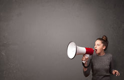 Girl shouting into megaphone on copy space background Royalty Free Stock Photos