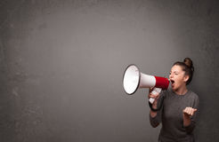 Girl shouting into megaphone on copy space background Stock Photography