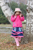 Girl shouting in park. Happy young girl in warm clothes shouting in park with birch tree in background Royalty Free Stock Photo
