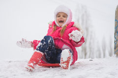 Girl shouting and rejoicing rolling ice slides. Seven-year girl riding on a snowy icy hill Stock Photography