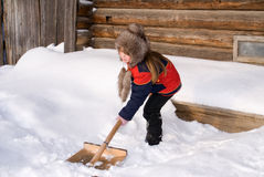 Girl with a shovel. The girl cleans a snow a shovel stock image