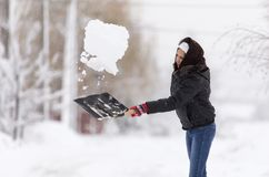 Girl with a shovel cleans the snow.  Royalty Free Stock Images