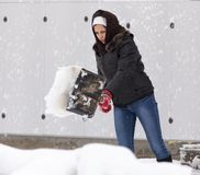 Girl with a shovel cleans the snow.  Stock Image