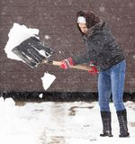 Girl with a shovel cleans the snow.  Stock Images