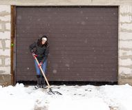 Girl with a shovel cleans the snow.  Royalty Free Stock Photography