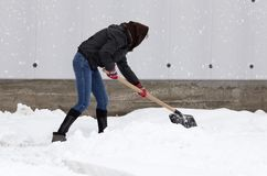 Girl with a shovel cleans the snow.  Stock Photos