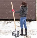 Girl with a shovel cleans the snow.  Royalty Free Stock Photos