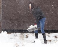 Girl with a shovel cleans the snow.  Royalty Free Stock Image