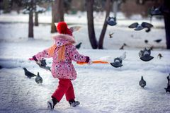 The girl in the park runs disperses pigeons in the winter. The girl with a shovel in the park runs disperses pigeons in the winter Royalty Free Stock Photos