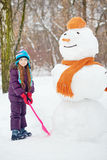 Girl with shovel stands next to big snowman Stock Photos