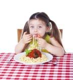 Girl shoving pasta Stock Photography