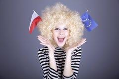 Girl show EU and Poland flag. Beautiful girl with ringlets show European Union and Poland flag. Studio shot Stock Image