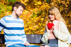 Girl show feelings to man in autumnal park. Royalty Free Stock Photos