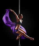 Girl show gymnastic exercise with pole dance Royalty Free Stock Image