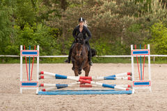 Girl is show jumping with her horse Stock Photo