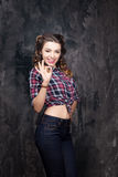Girl show ok sign in checkered shirt and jeans. In studio Royalty Free Stock Photos