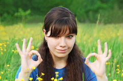 Girl show OK symbol. Portrait of young woman showing OK gesture at nature Stock Photo