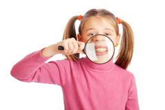 Girl show their teeth through a magnifying glass. Beautiful girl on a white background shows the teeth through a magnifying glass Royalty Free Stock Images