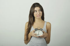 Girl showing alarm clock with worried expression. Royalty Free Stock Photography