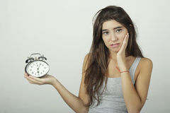 Girl showing alarm clock with worried expression. Royalty Free Stock Images