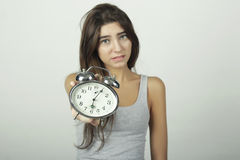 Girl showing alarm clock with worried expression. Stock Photos