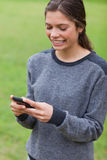 Girl showing a beaming smile while sending a text Stock Images