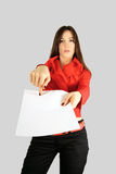 Girl showing blank paper. Beauty girl in red showing on blank paper with empty space for text or adv. Isolated on grey (because of white paper royalty free stock photography