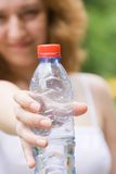 Girl showing a bottle of water Royalty Free Stock Images