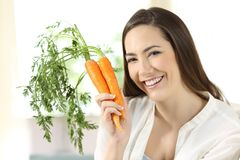 Girl showing a bundle of carrots looking at camera Royalty Free Stock Photo