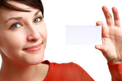 Girl showing business card. Smiling brunette showing blank business card stock photo