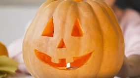 Girl showing carved jack pumpkin with burning candle inside, preparing for party. Stock footage stock footage