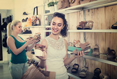 girl showing a chosen pair of shoes. Brunette girl showing a chosen pair of shoes while her friend still choosing royalty free stock image