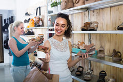 girl showing a chosen pair of shoes. Brunette girl showing a chosen pair of shoes while her friend still choosing royalty free stock photo
