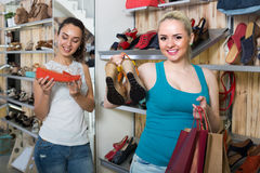 Girl showing a chosen pair of shoes. Cheerful customer showing a chosen pair of shoes while her friend still choosing royalty free stock images