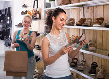 girl showing a chosen pair of shoes. cheerful girl showing a chosen pair of shoes while her friend still choosing royalty free stock photography