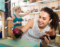 girl showing a chosen pair of shoes. smiling cheerful girl showing a chosen pair of shoes while her friend still choosing stock images