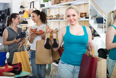 Girl showing a chosen pair of shoes. Spanish cheerful girl showing a chosen pair of shoes while her friend still choosing royalty free stock image
